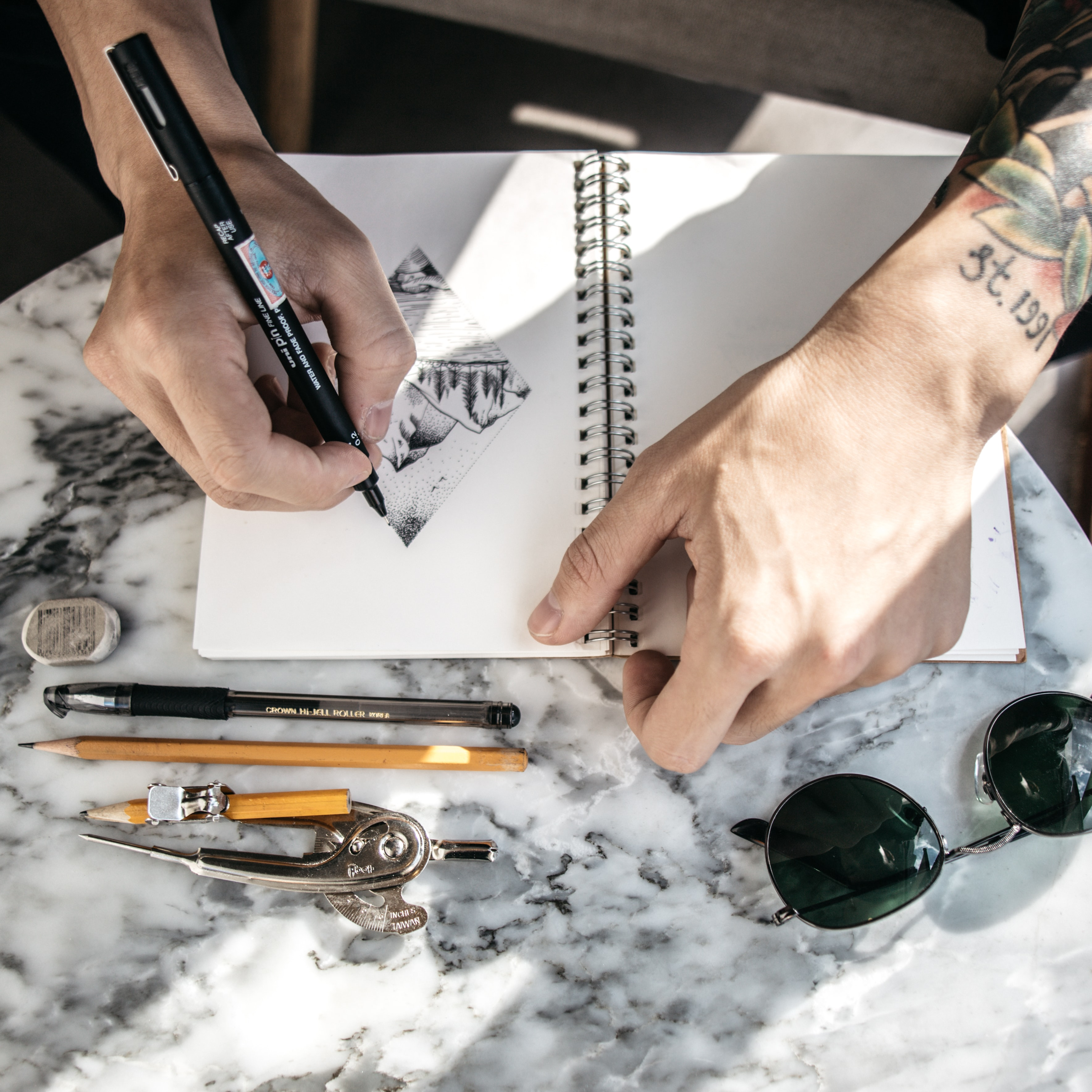person sketching on notebook using pen