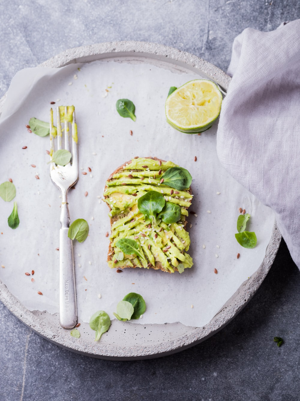 wheat bread with avocado spread beside white plastic spoon and pressed lime on round white plate