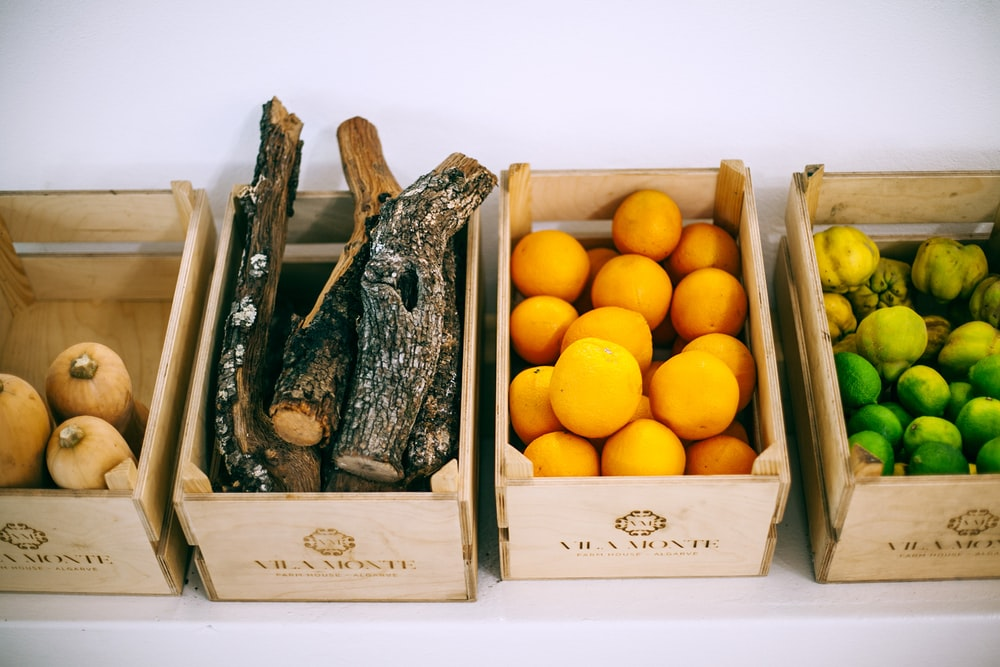 assorted fruits on brown wooden crates