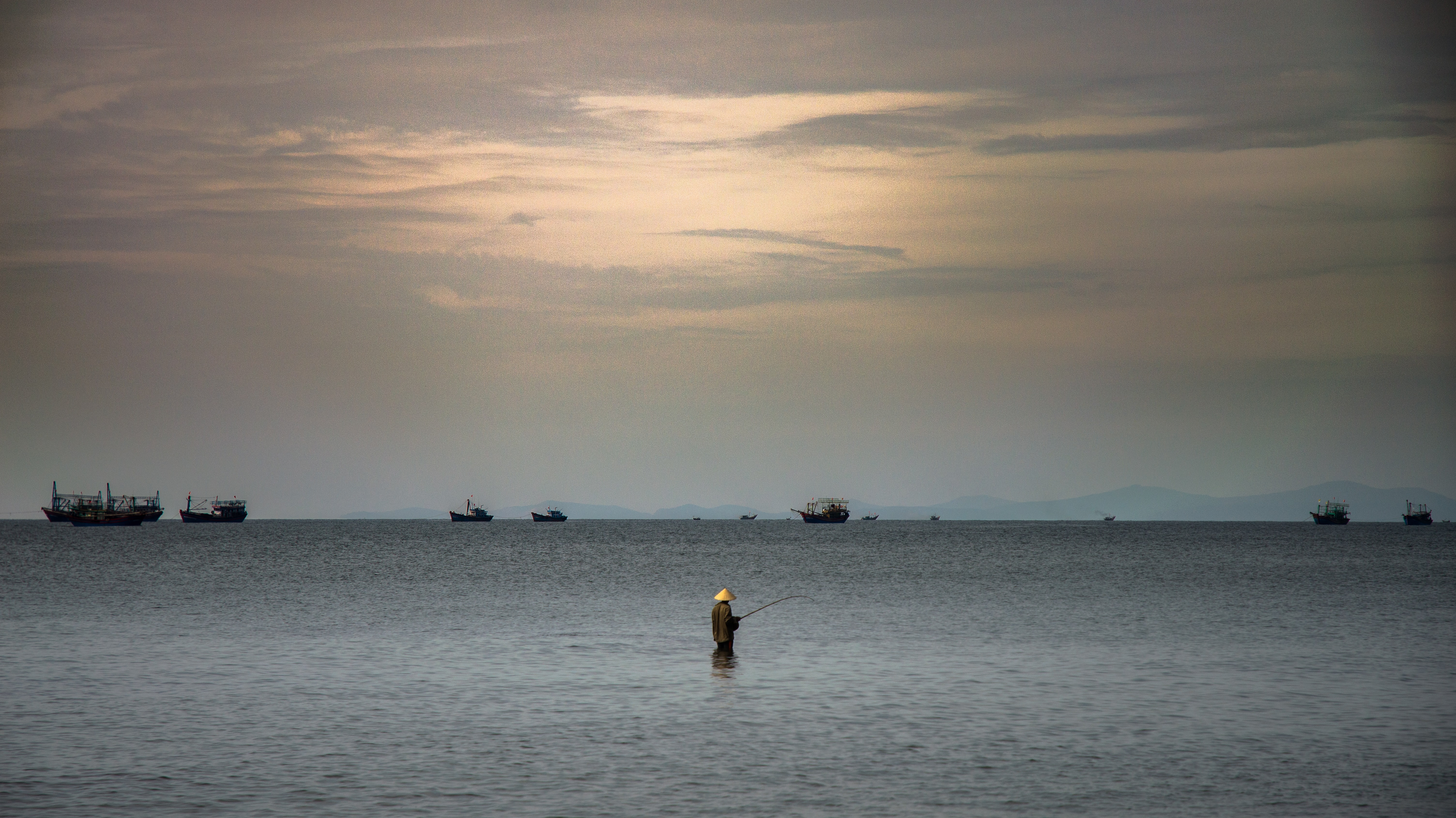 person fishing in the middle of body of water