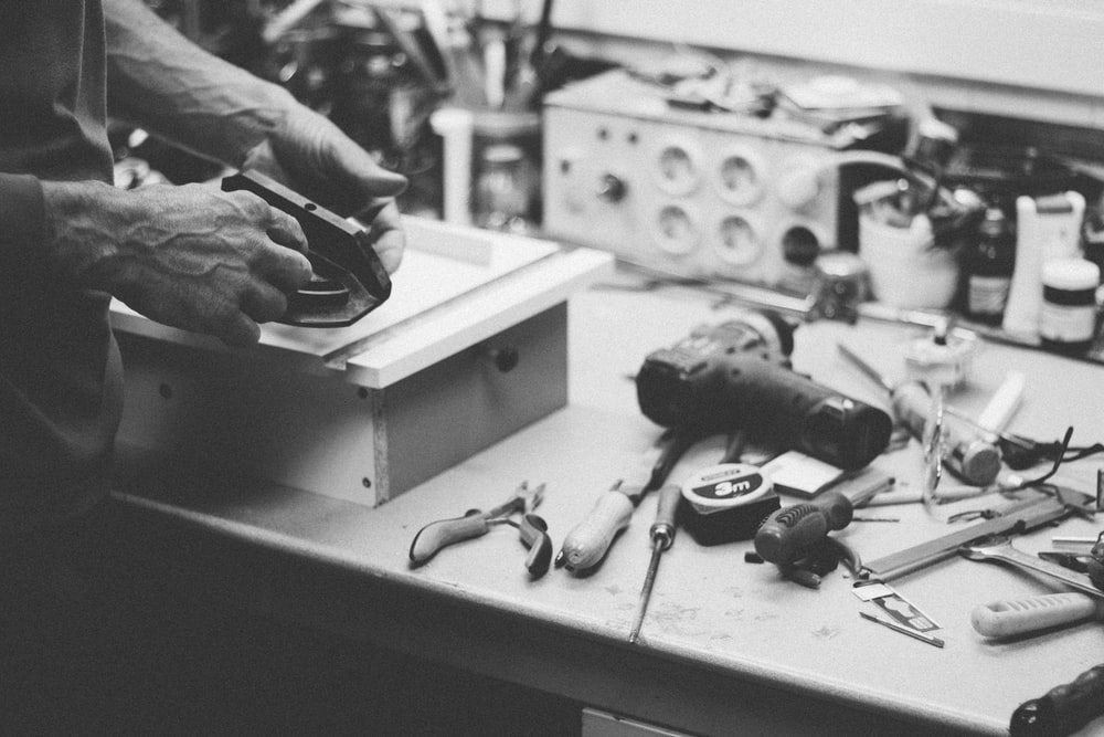 grayscale photo of person standing beside power tools on table