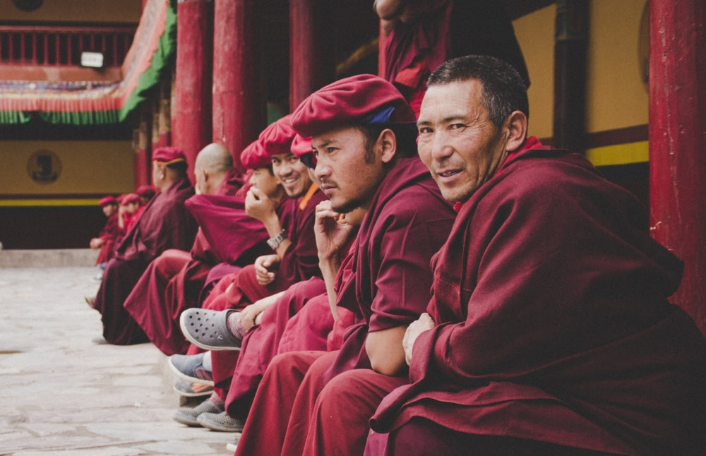 group of men wearing red dress sitting at the temple smiling while taking selfie
