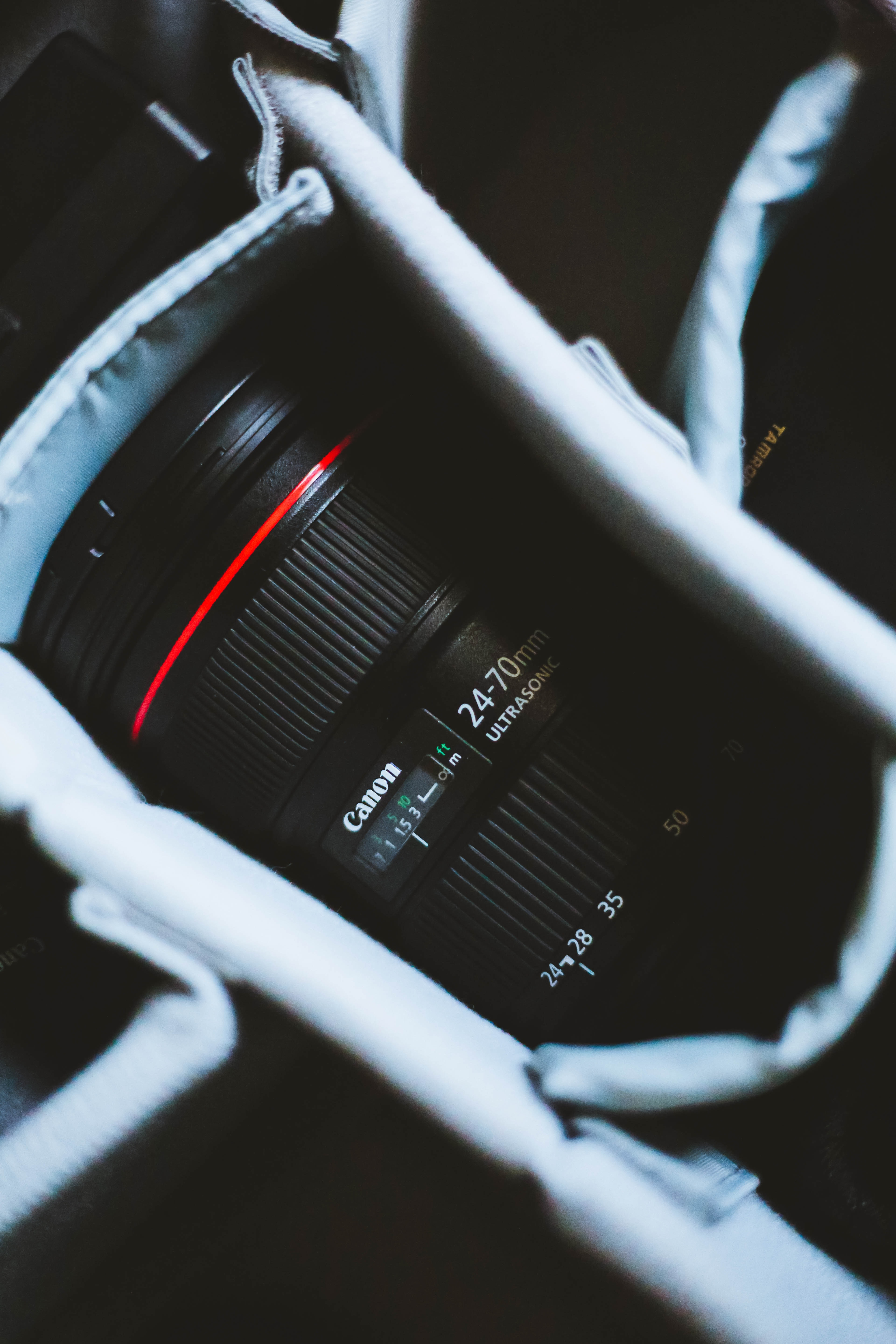 black and red Canon zoom lens in bag