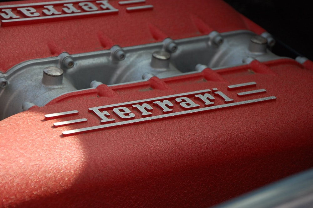 close-up photography of gray and red Ferrari engine