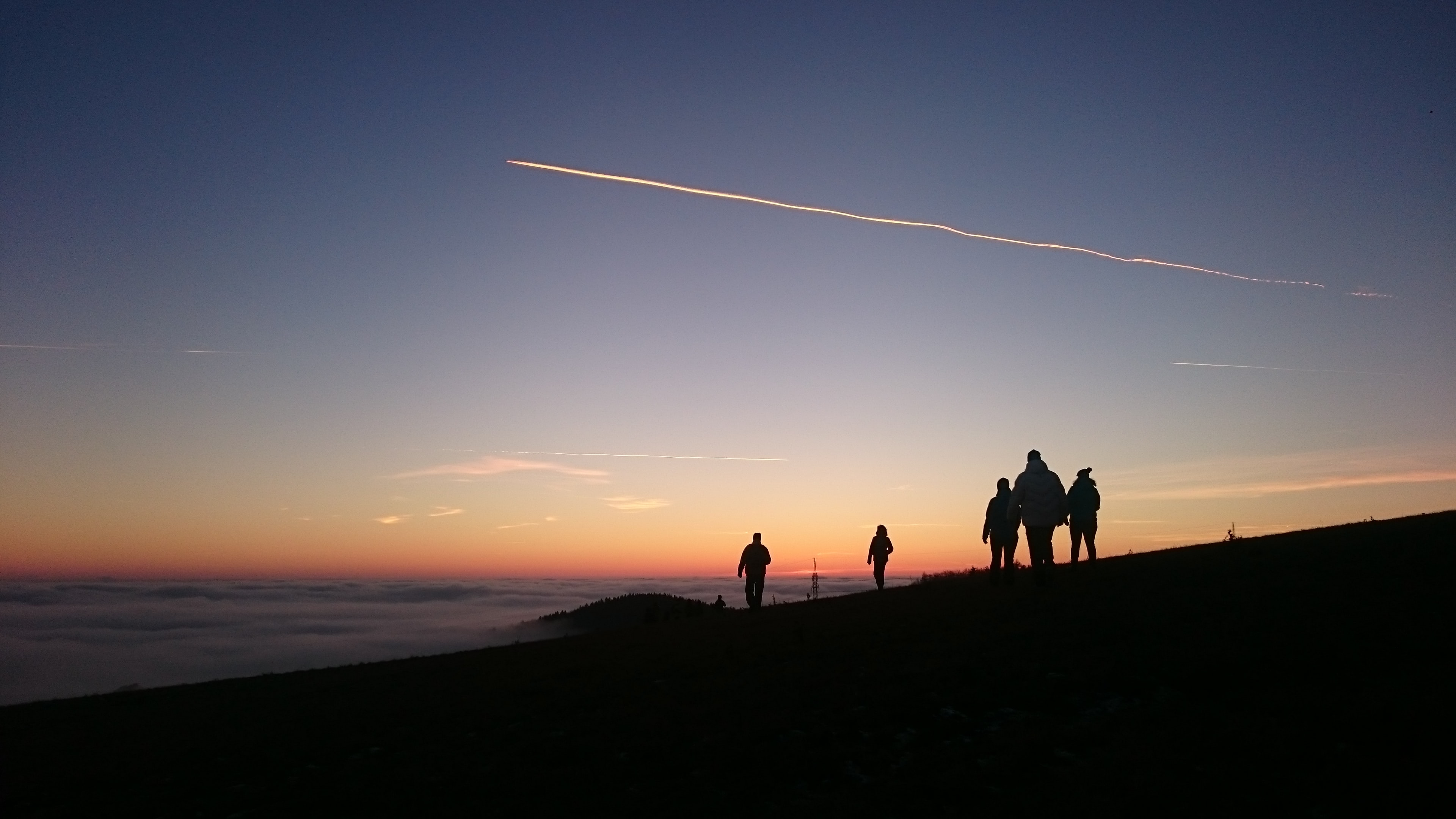 silhouette photo of group of five people walking on mountain during sunset