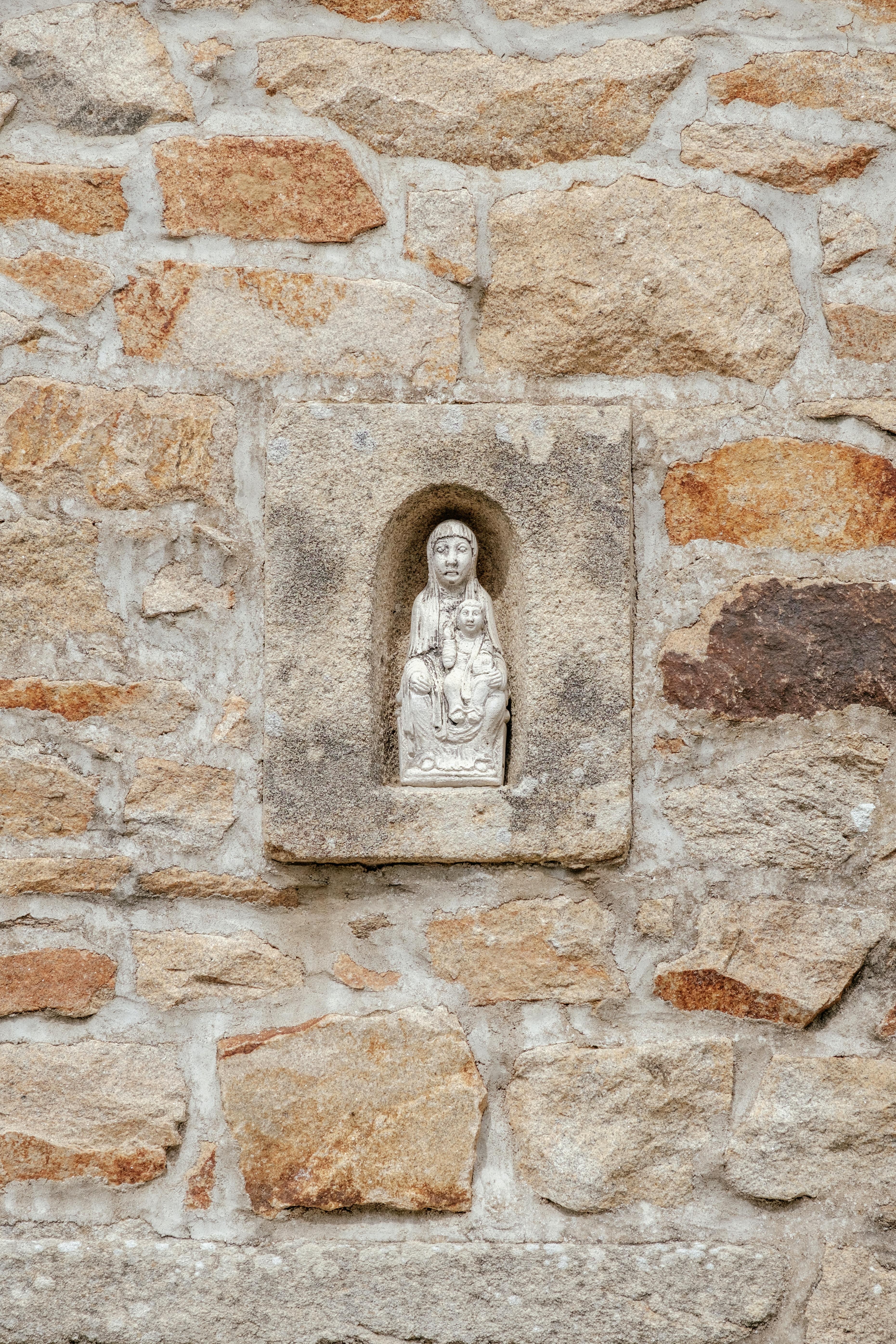 religious figure on gray concrete wall taken at daytime