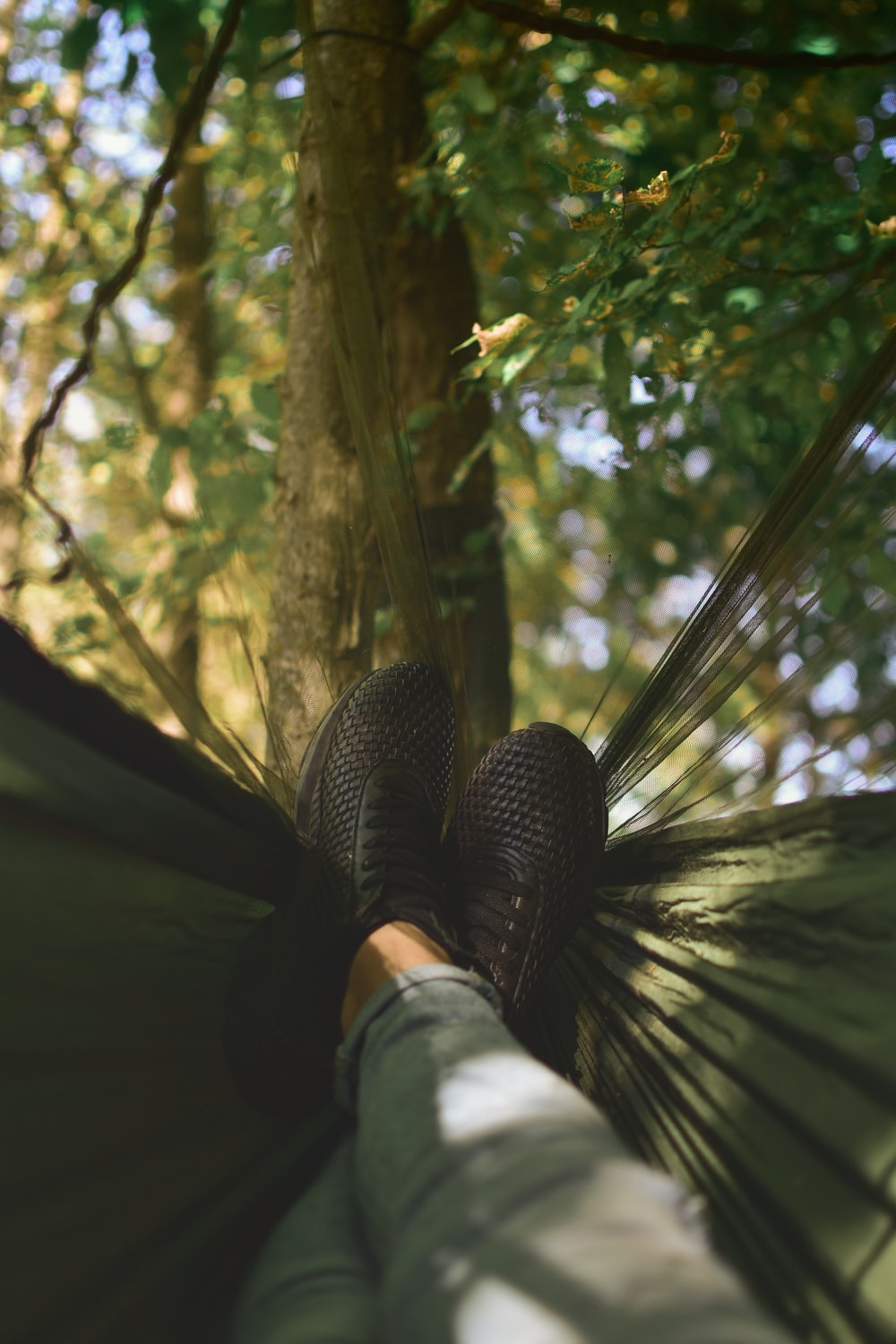 person on camping hammock tied on tree