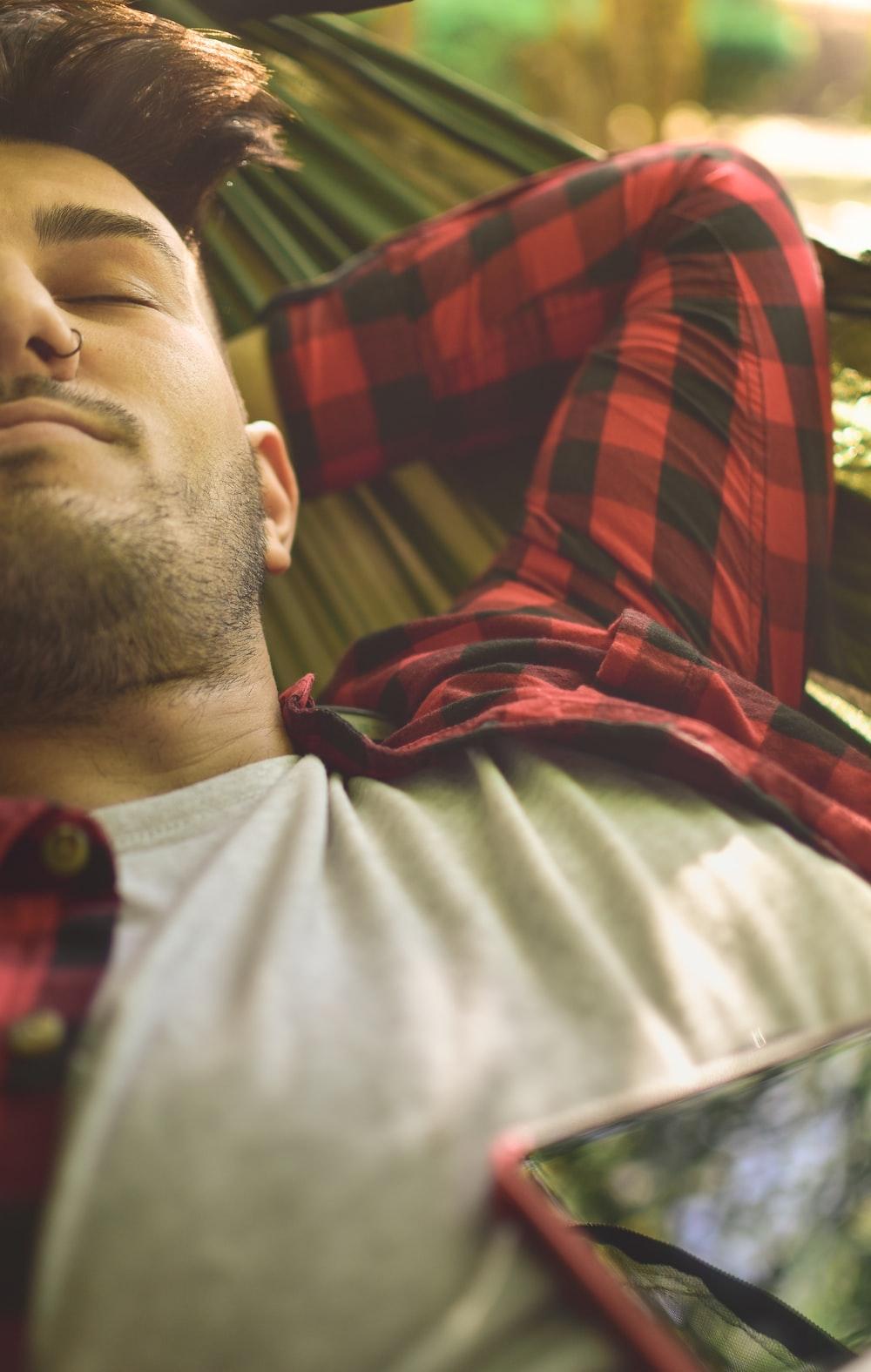 close photography of man lying on green hammock