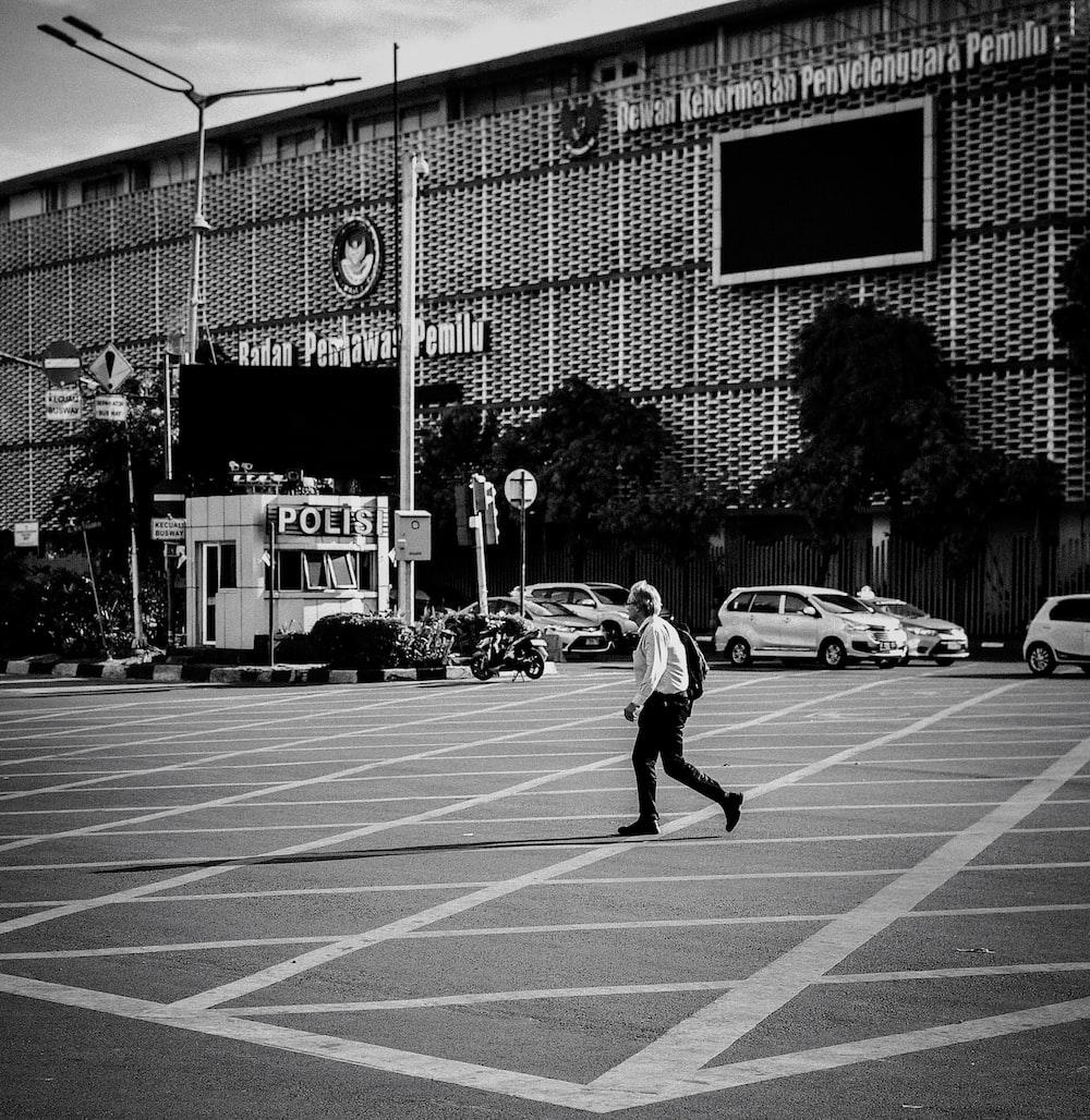 grayscale photo of man walking beside building