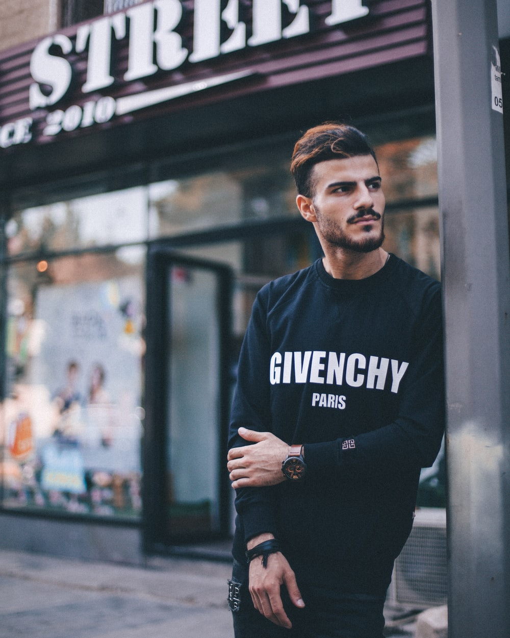 man in black Givenchy sweatshirt standing beside of post in front of Strek store during daytime shallow focus photography