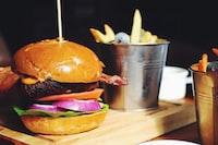 hamburger near gray stainless steel bucket filled with potato fries