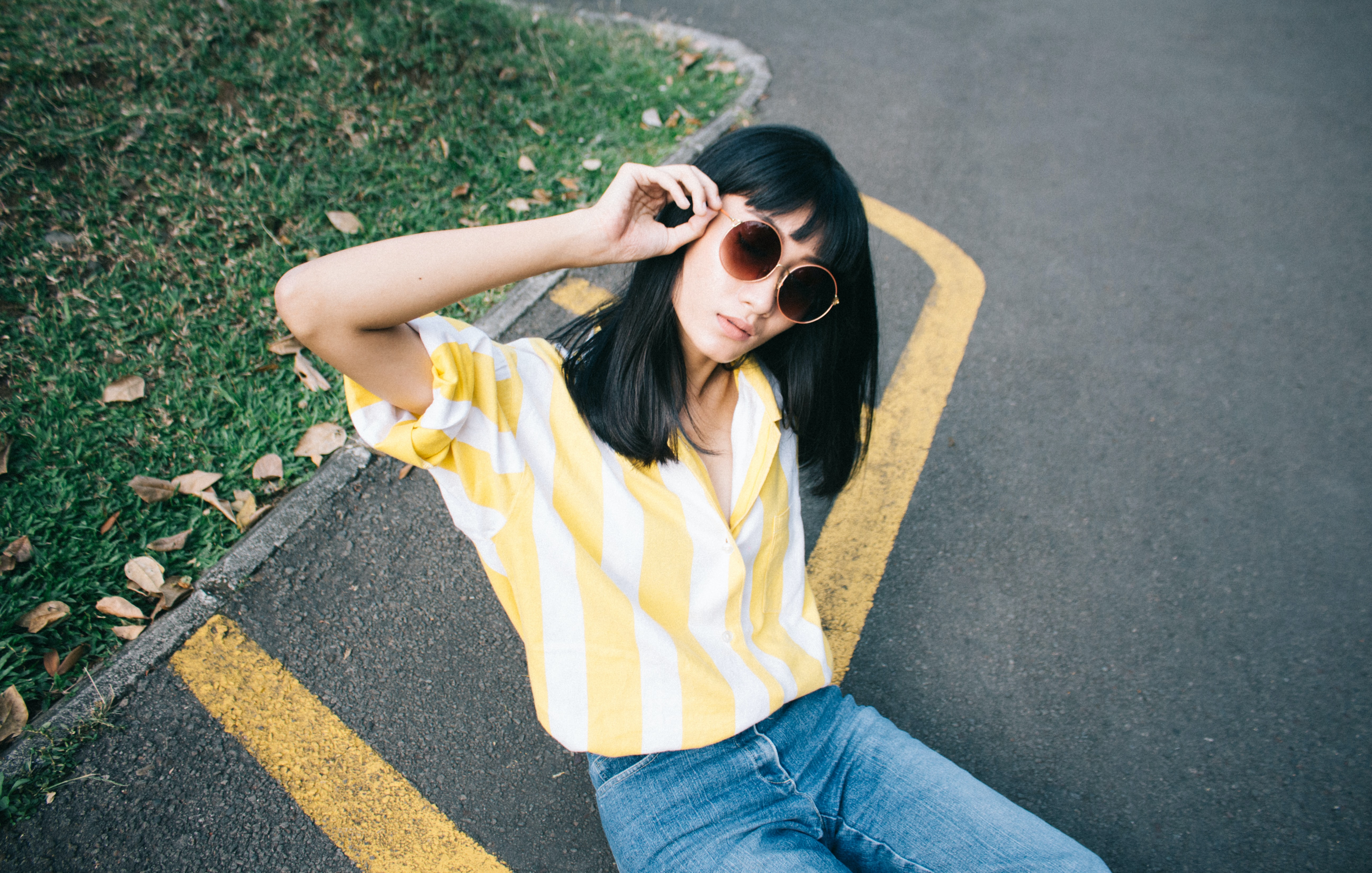 woman wearing yellow and white striped collared shirt holding round-shaped brown sunglasses sitting on gray concrete pavement during daytime