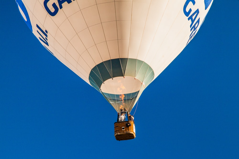 person inside brown, white, and green hot air balloon low angle photography