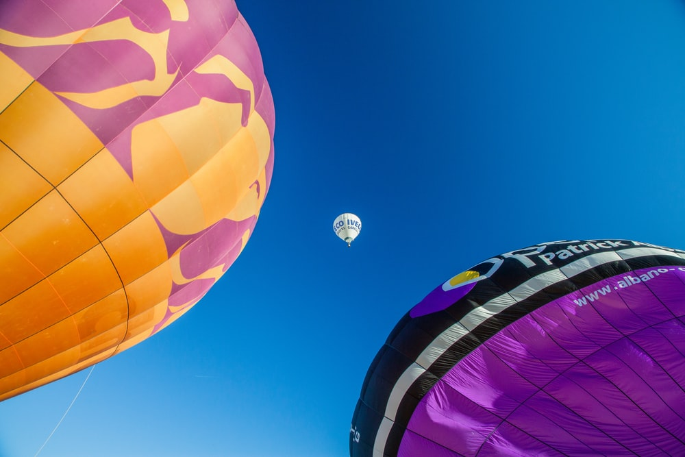 three assorted-color hot air balloons under blue sky
