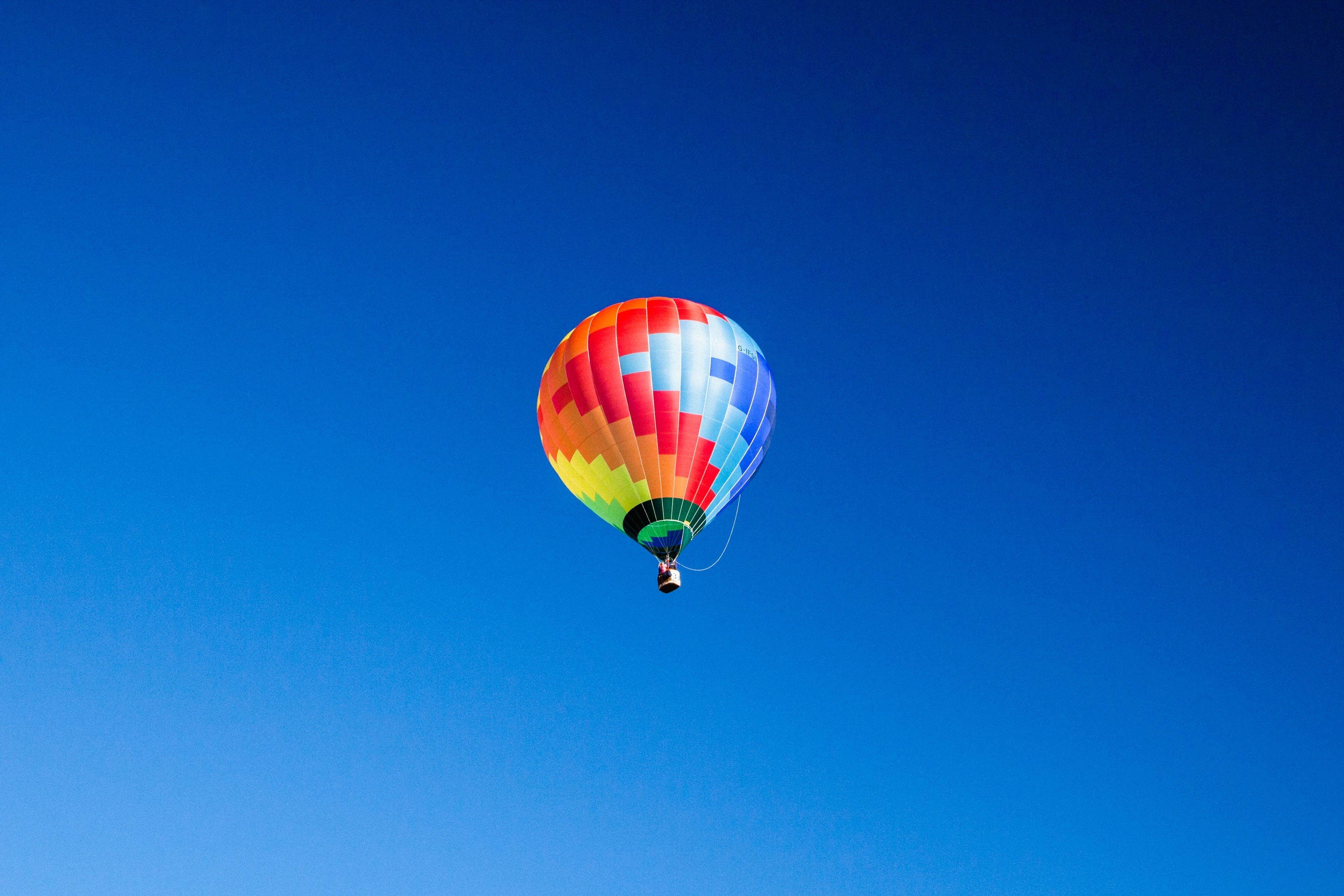 blue, orange, and red hot air balloon in mid air