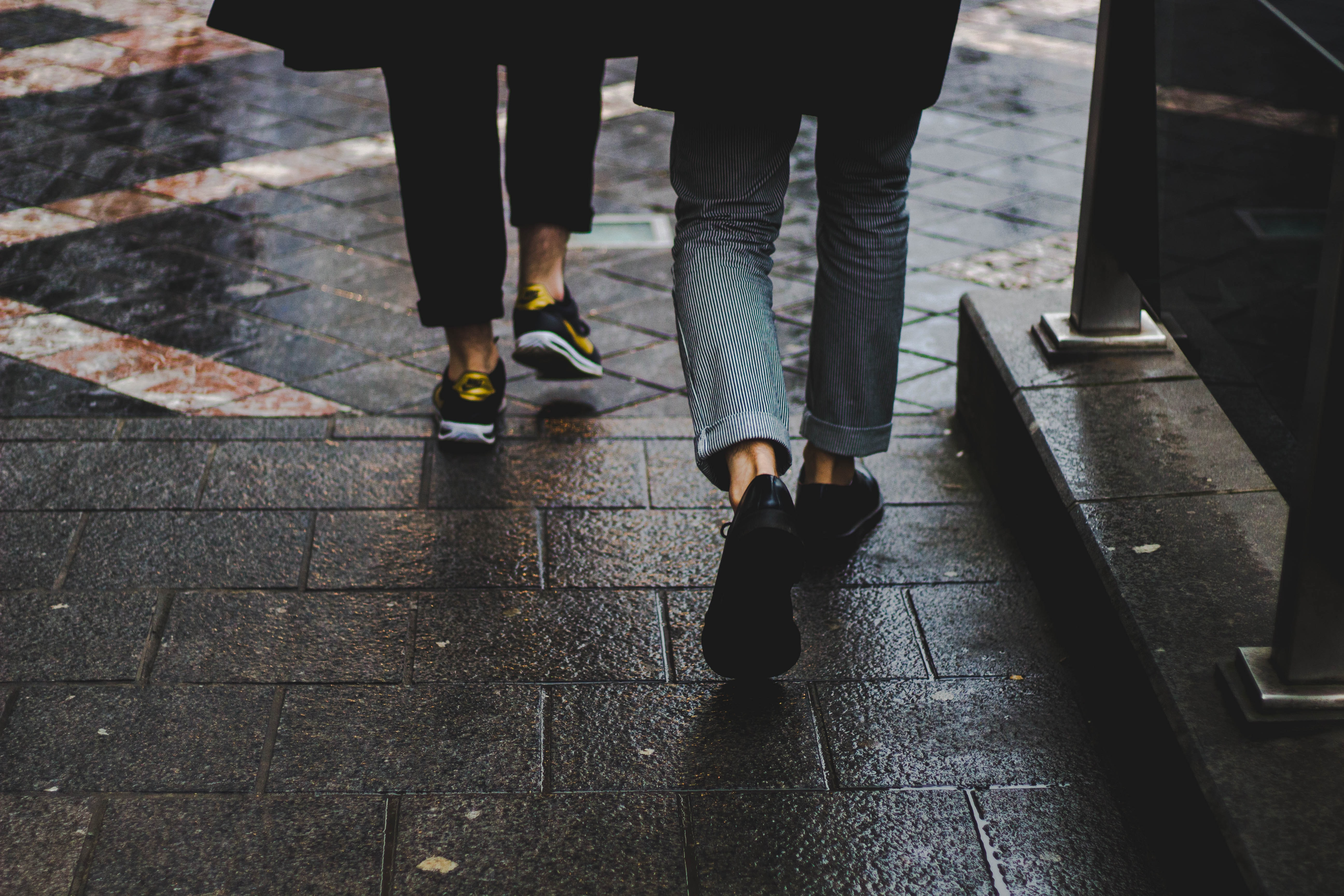 two person walking near the bench