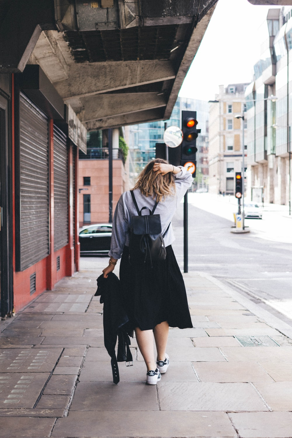 woman wearing gray dress shirt with black skirt and black backpack