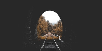 low-light photo of railroad tunnel