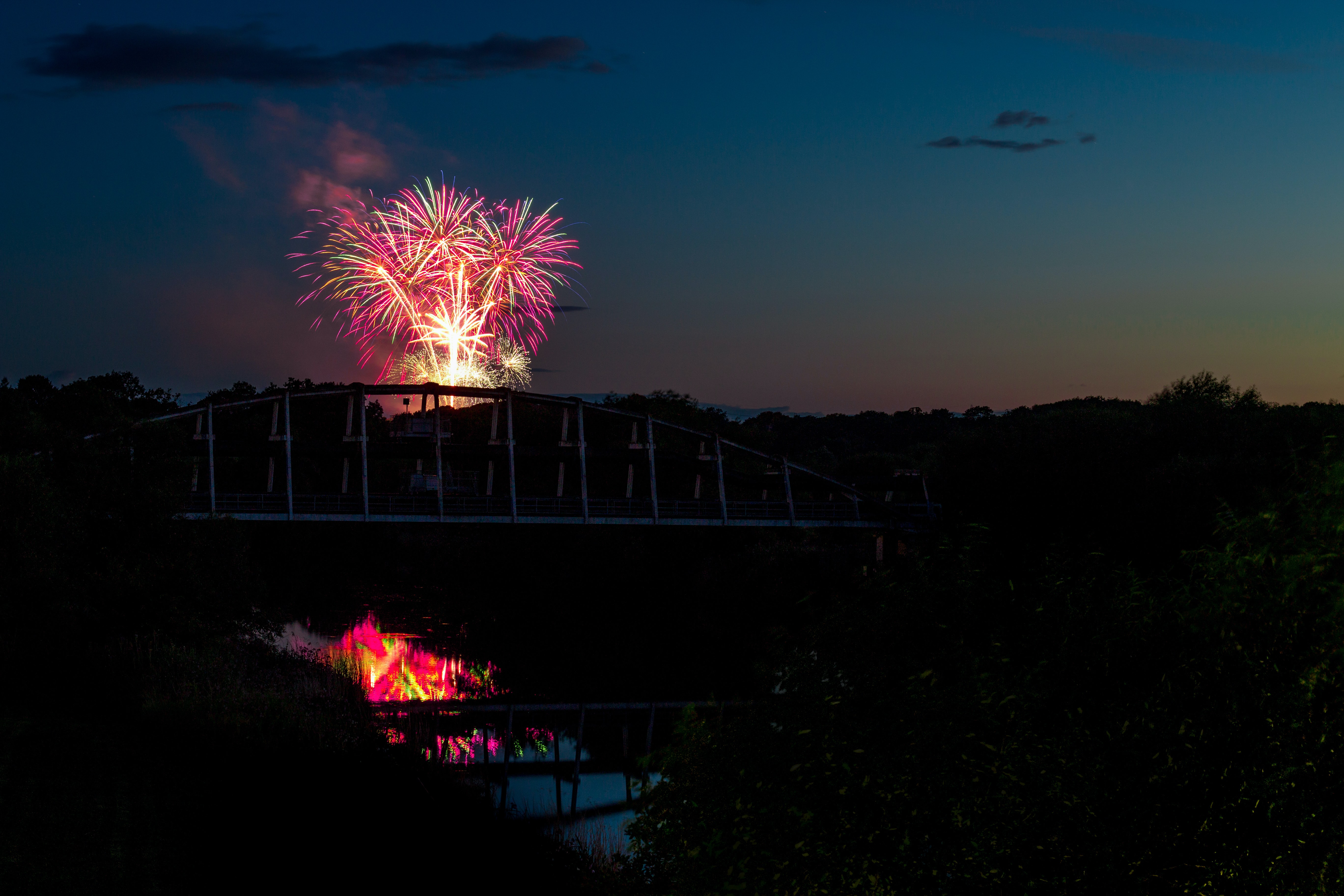 silhouette photo of suspension bridge in front of fireworks