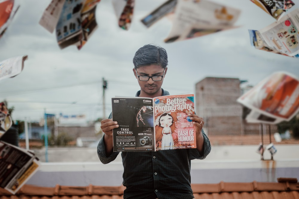 man reading magazine while standing
