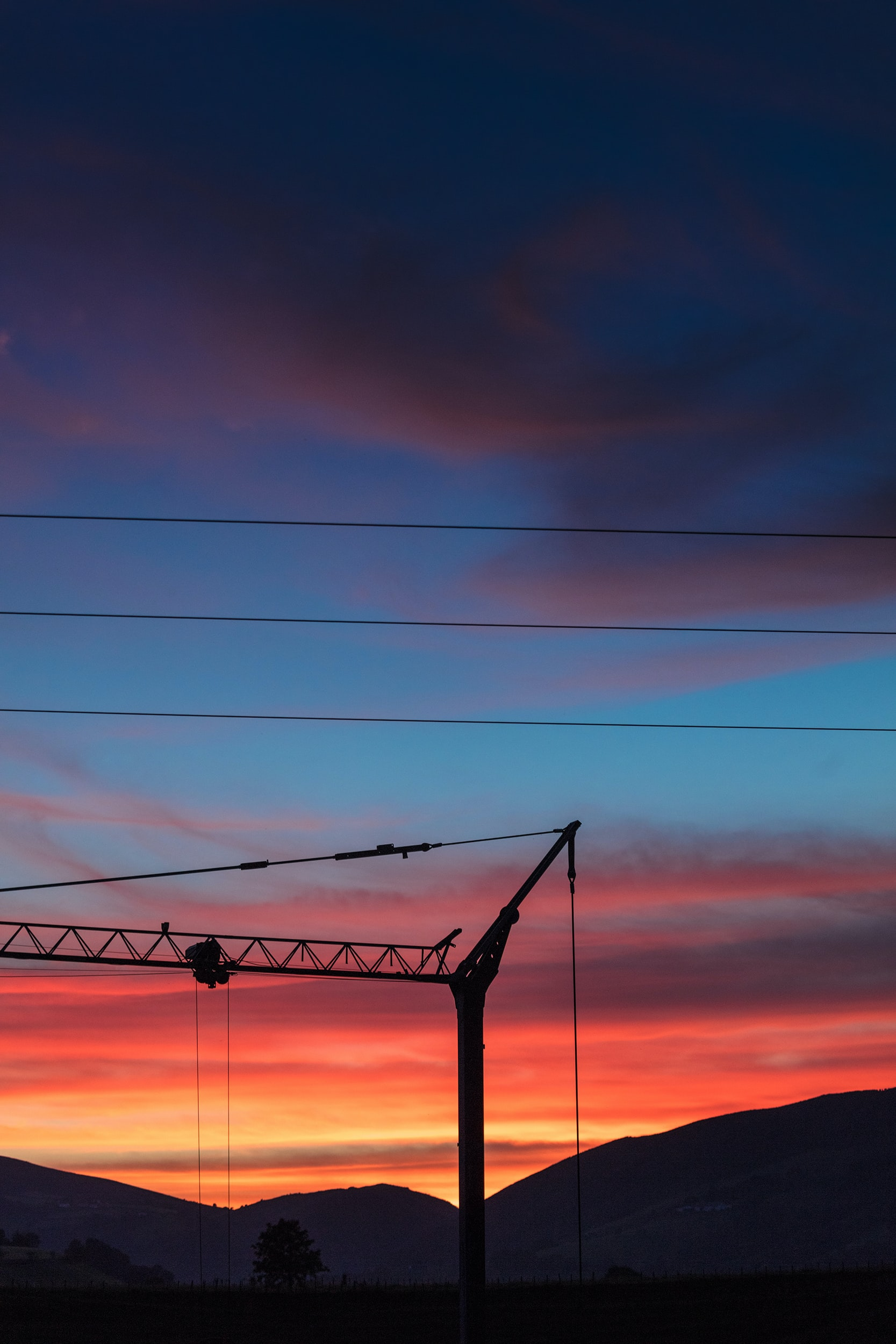 silhouette photo of electric post at golden hour