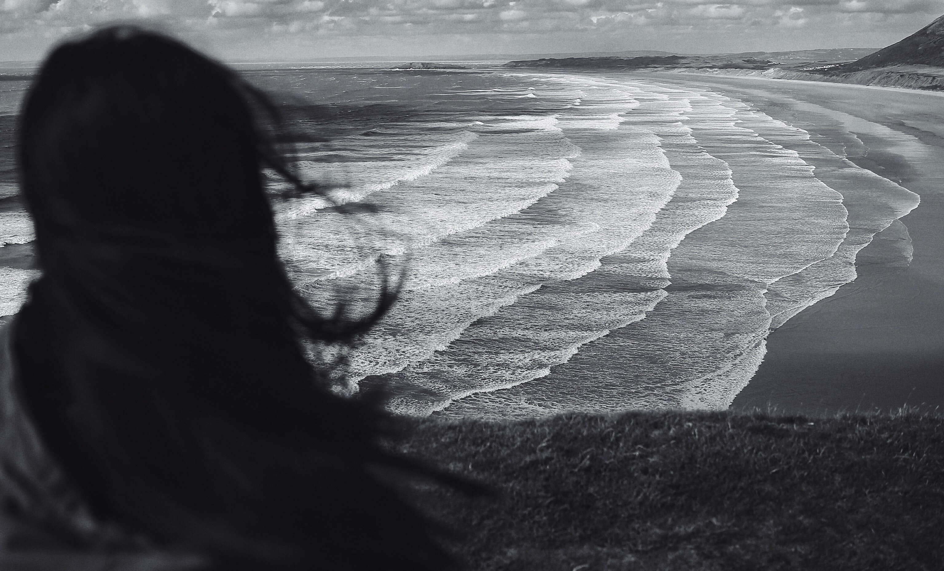grayscale photo of woman standing near seashore