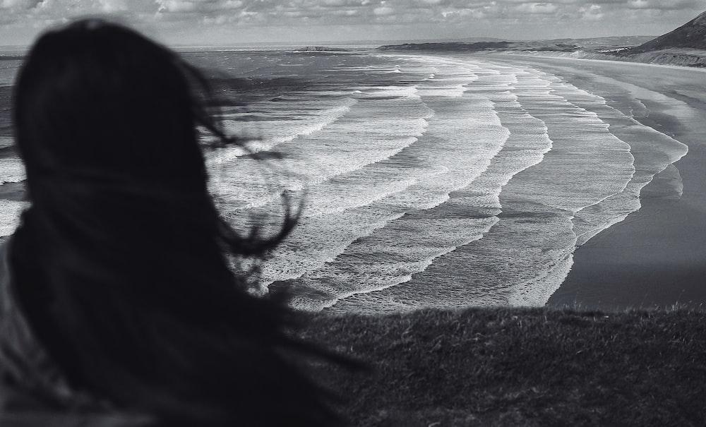 grayscale photo of woman standing near seashore