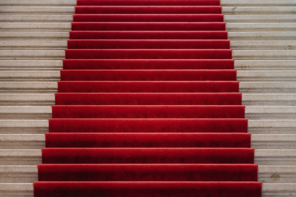 white concrete stair with red carpet