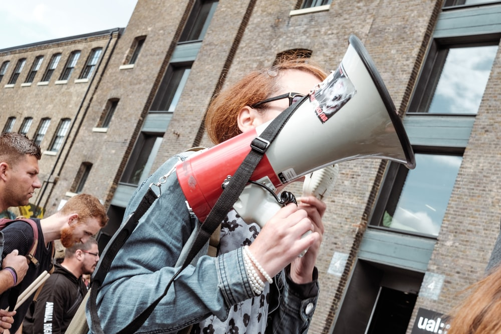 woman holding red and white megaphone standing near building