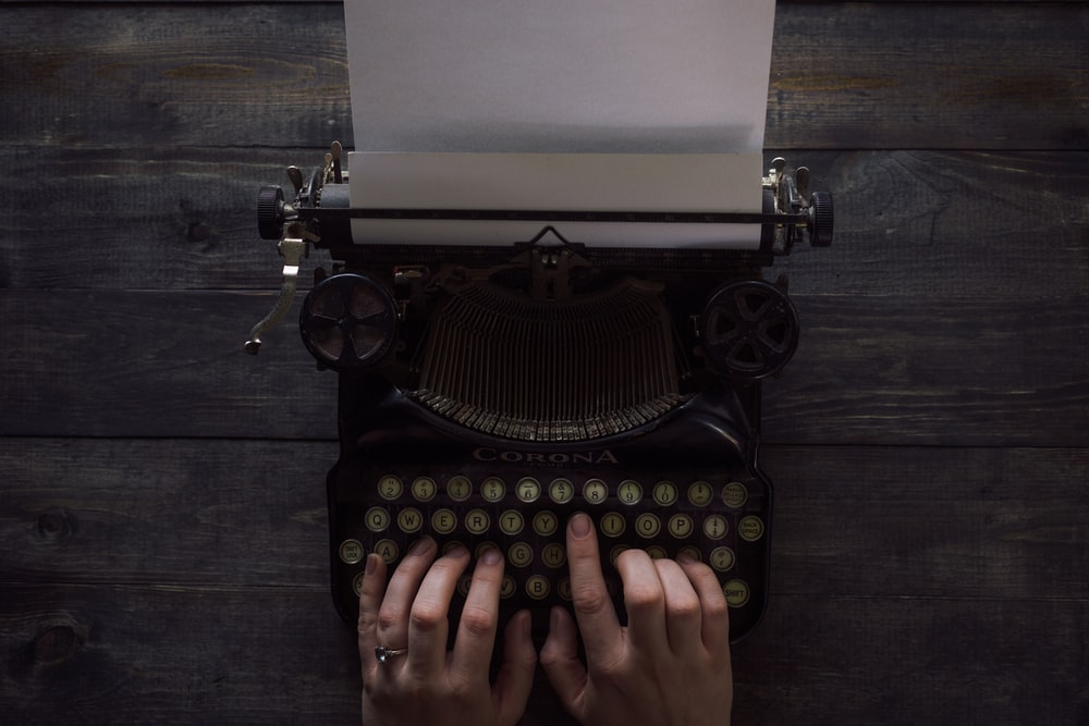 person holding white and black typewriter