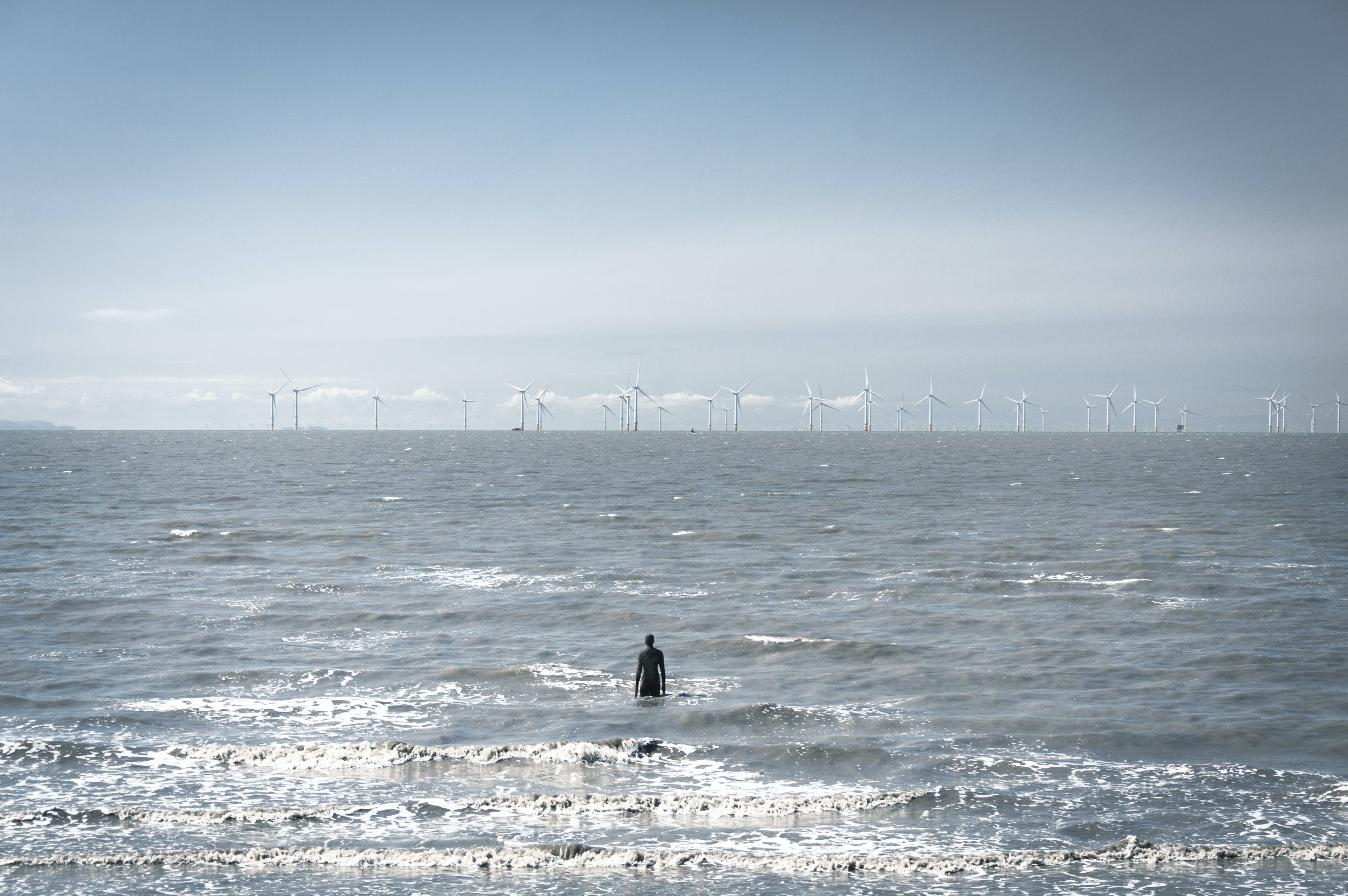 person on body of water in front of windmills during daytime
