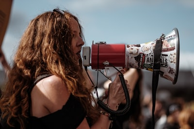 selective focus photography of woman wearing black cold-shoulder shirt using megaphone during daytime protest zoom background