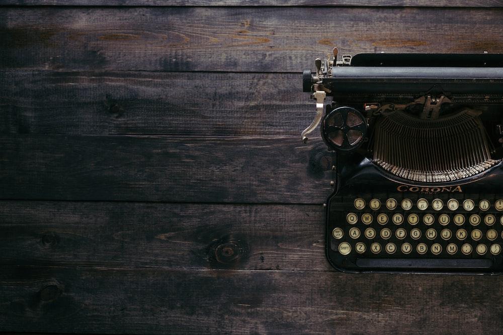 black Corona typewriter on brown wood planks