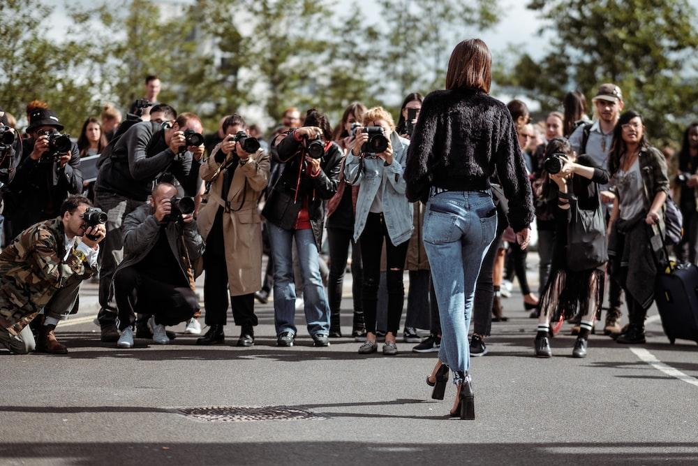 woman walking taking photo by people