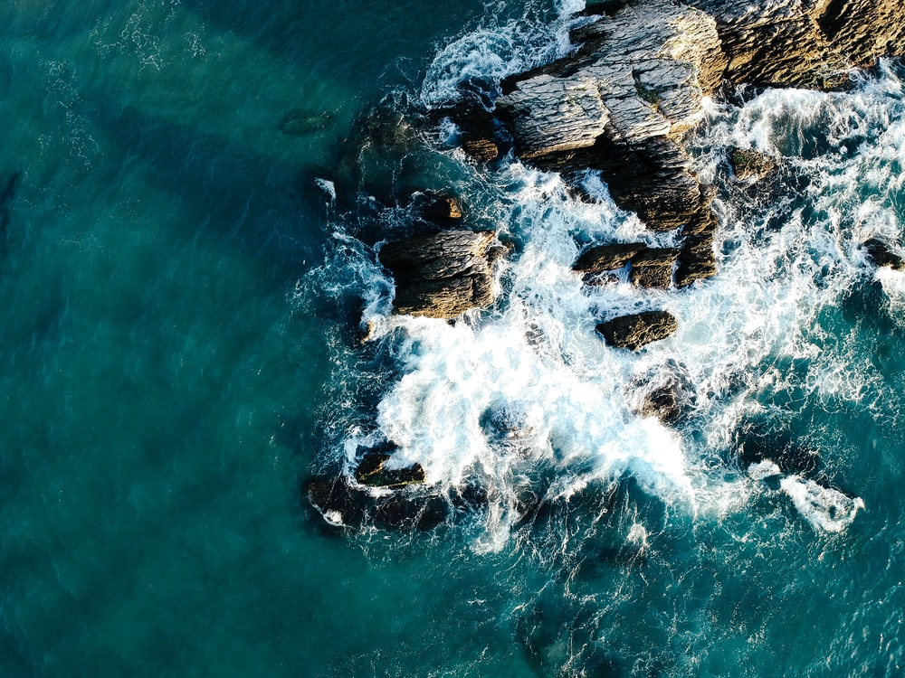 aerial view photo of rocks near body of water