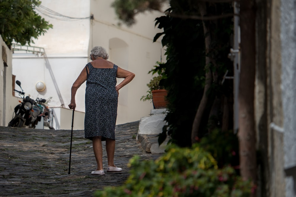 woman walking while holding cane near tall tree