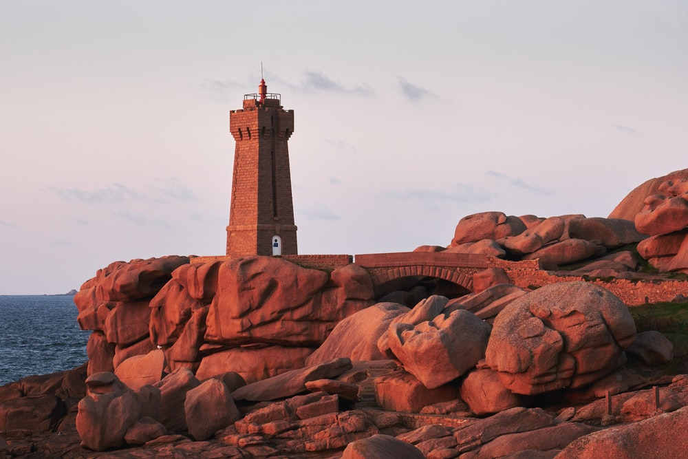 brown lighthouse on rock cliff near body of water