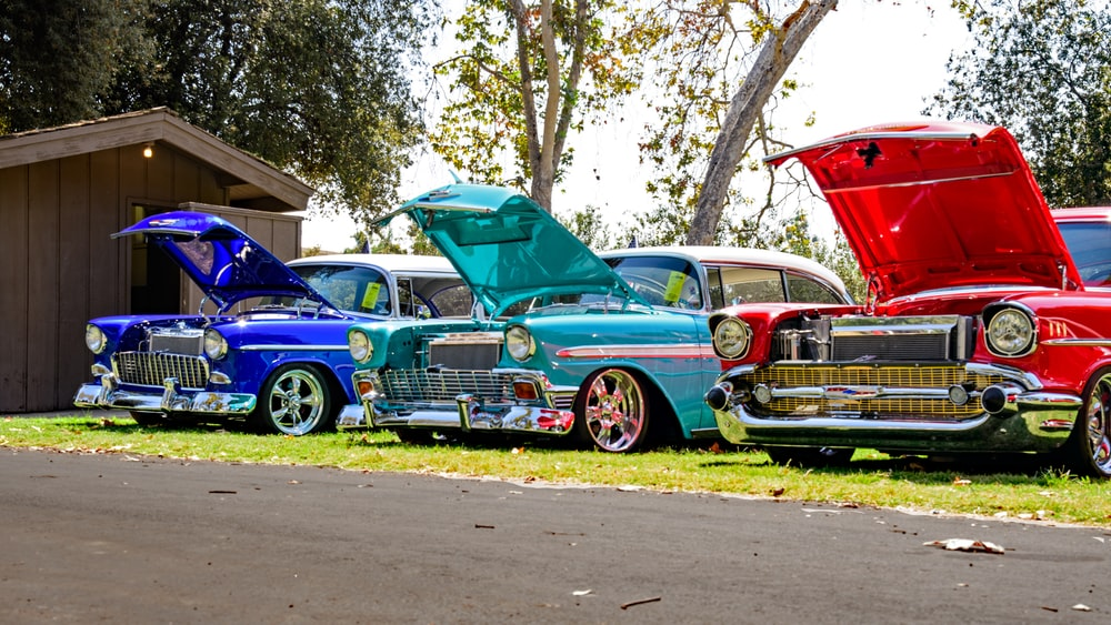 three red, blue, and teal classic cars