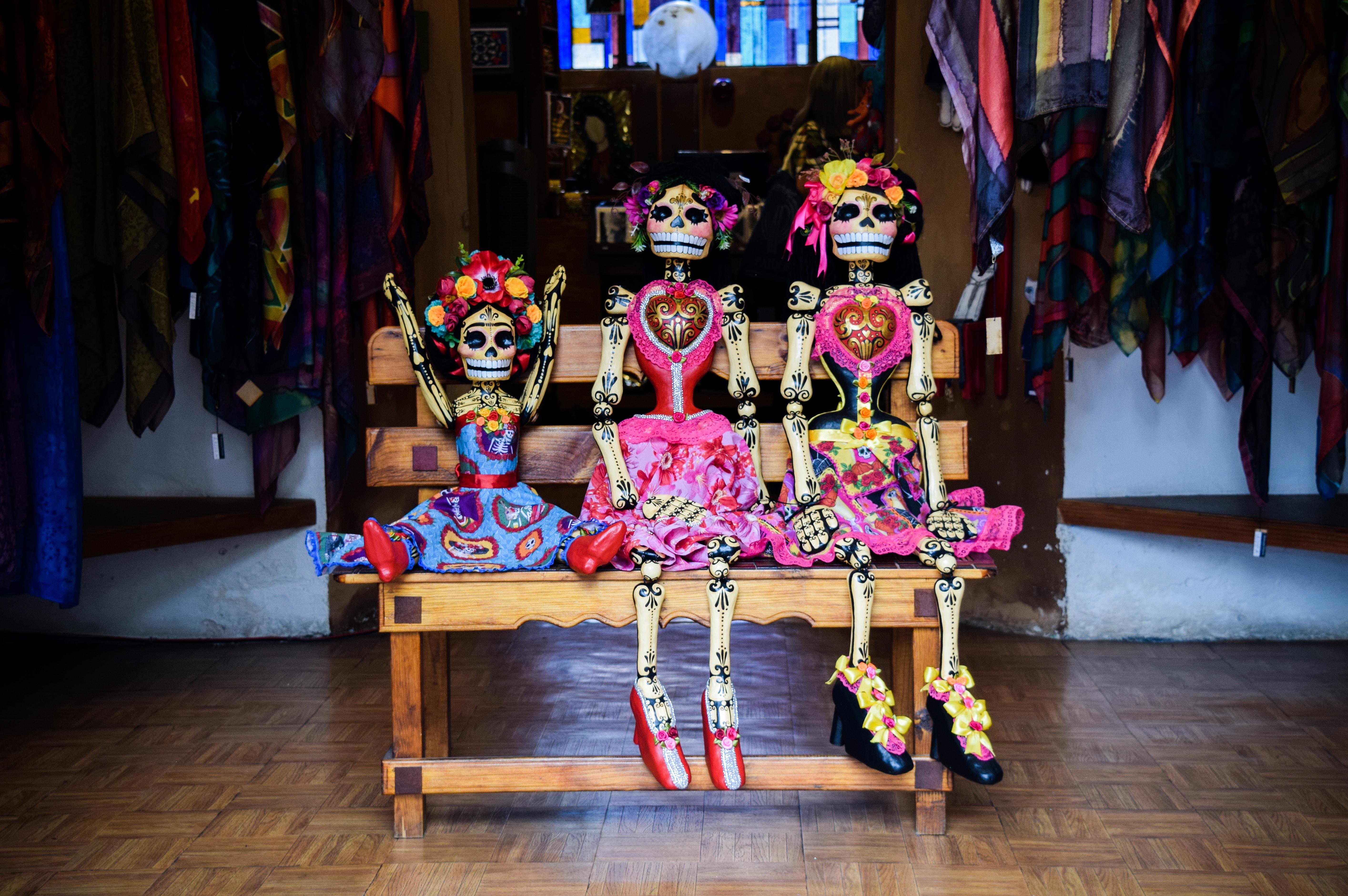 three Frida Kahlo skeleton dolls sitting on bench