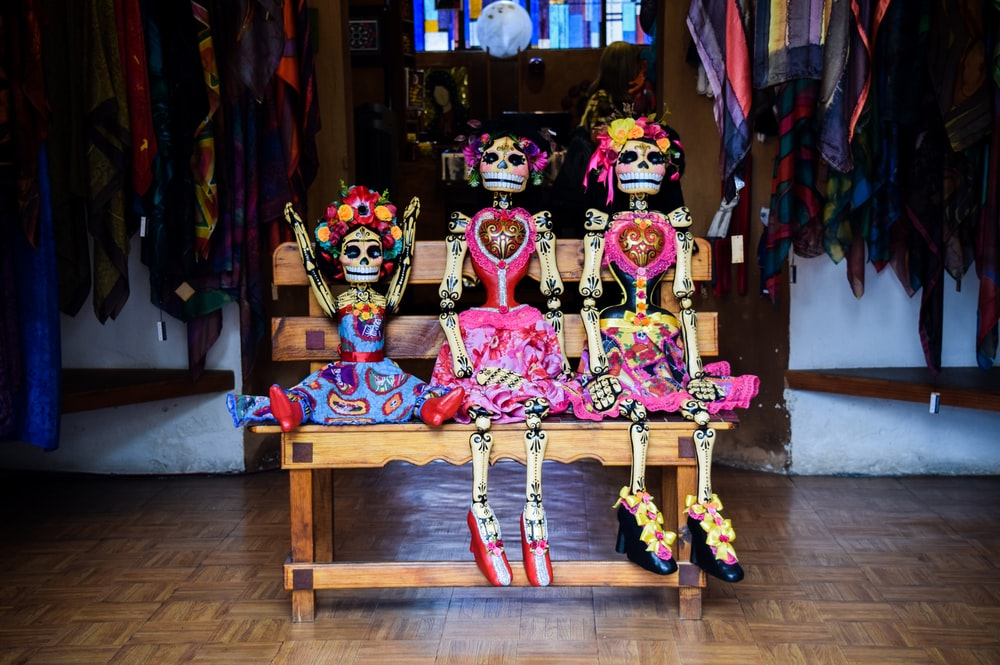 three Frida Kahlo skeleton dolls sitting on bench