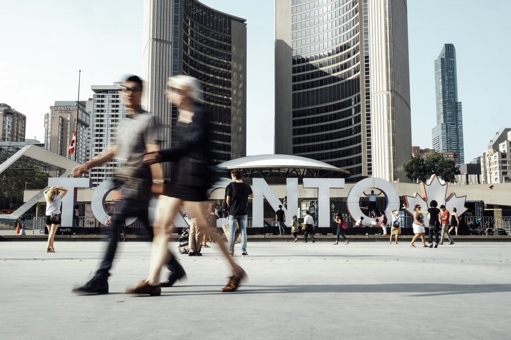 two man and woman walking on pathway near high rise buildings