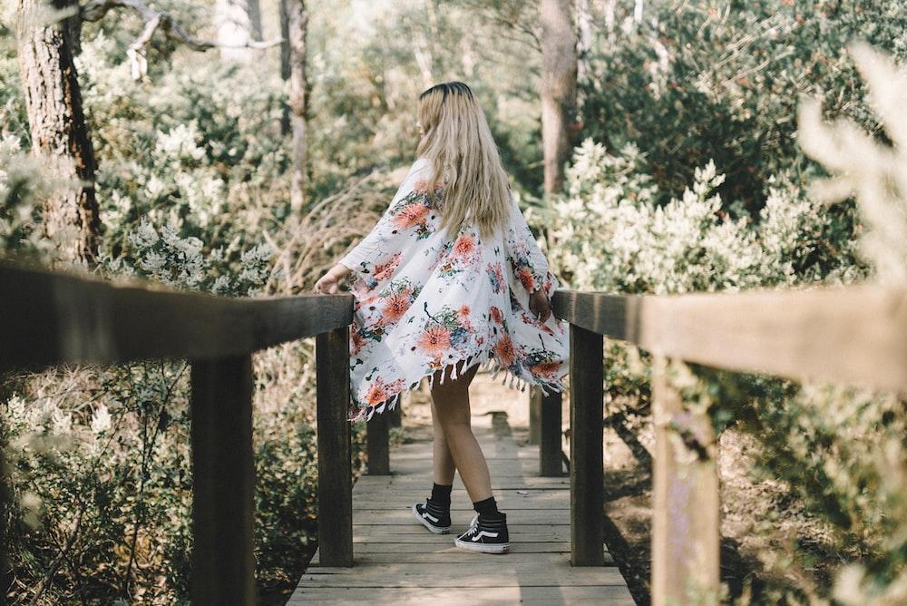 woman walking along wooden foot bridge leading to forest