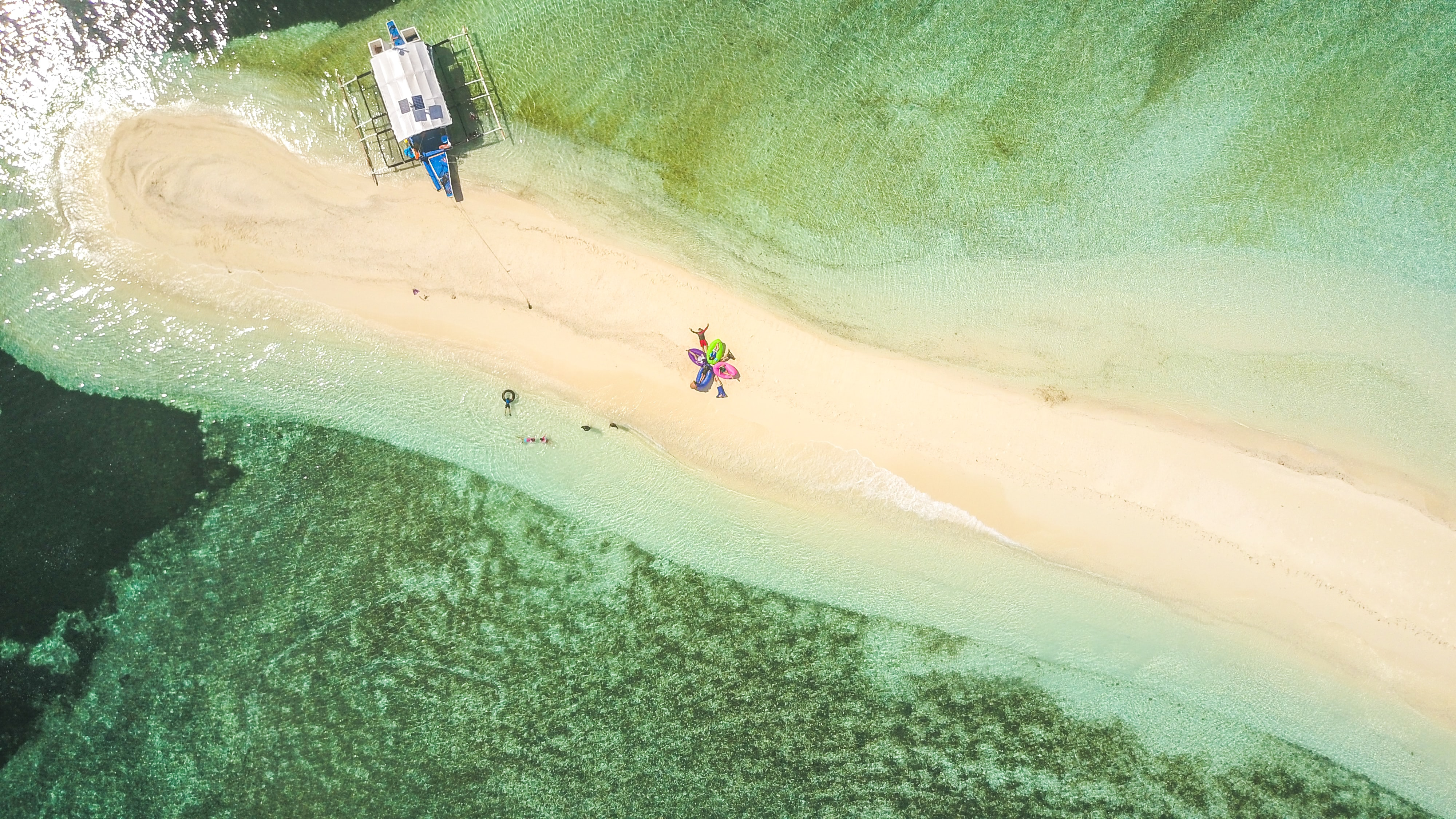 aerial photography of white and blue boat on seashore during daytime