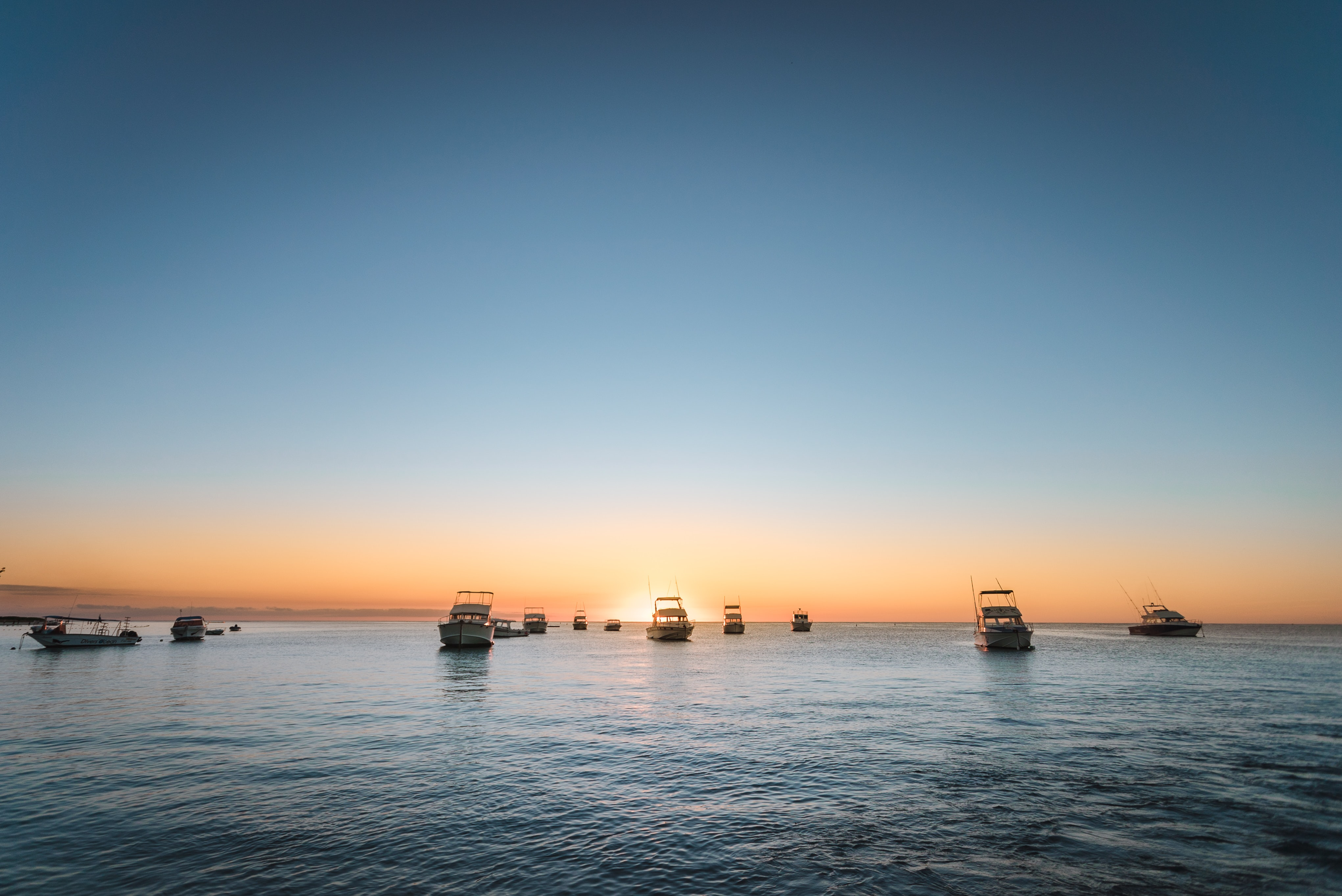 photo of boats under clear blue sky