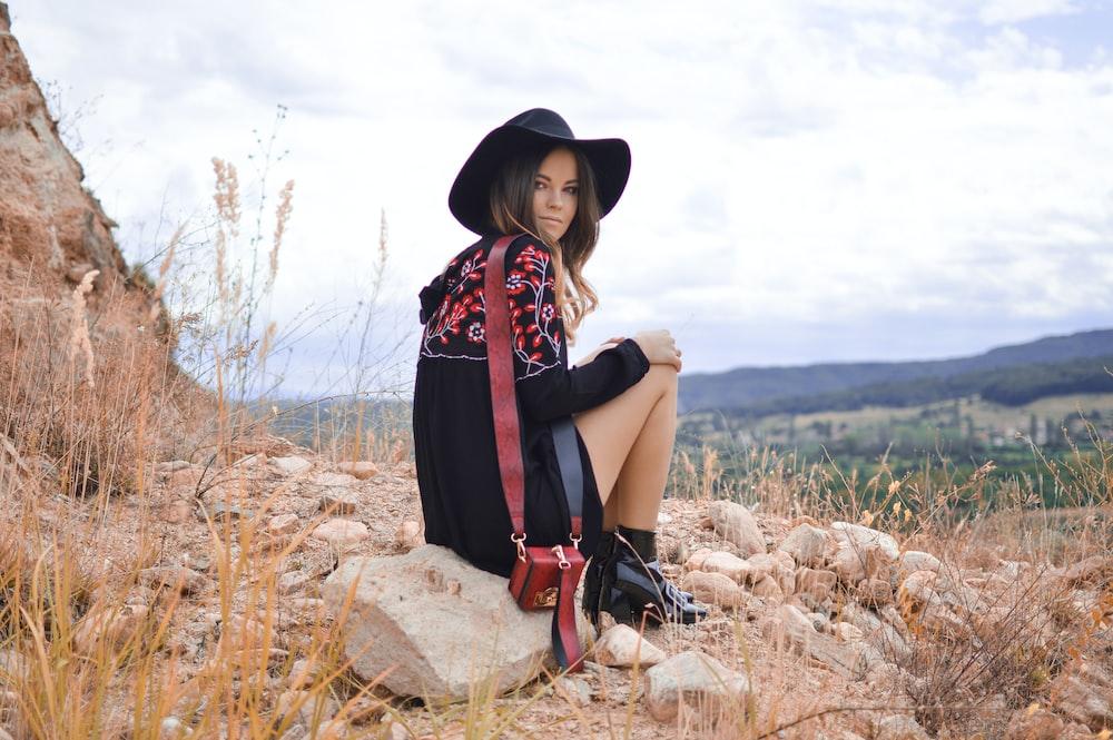 woman sitting on gray boulder near brown grass