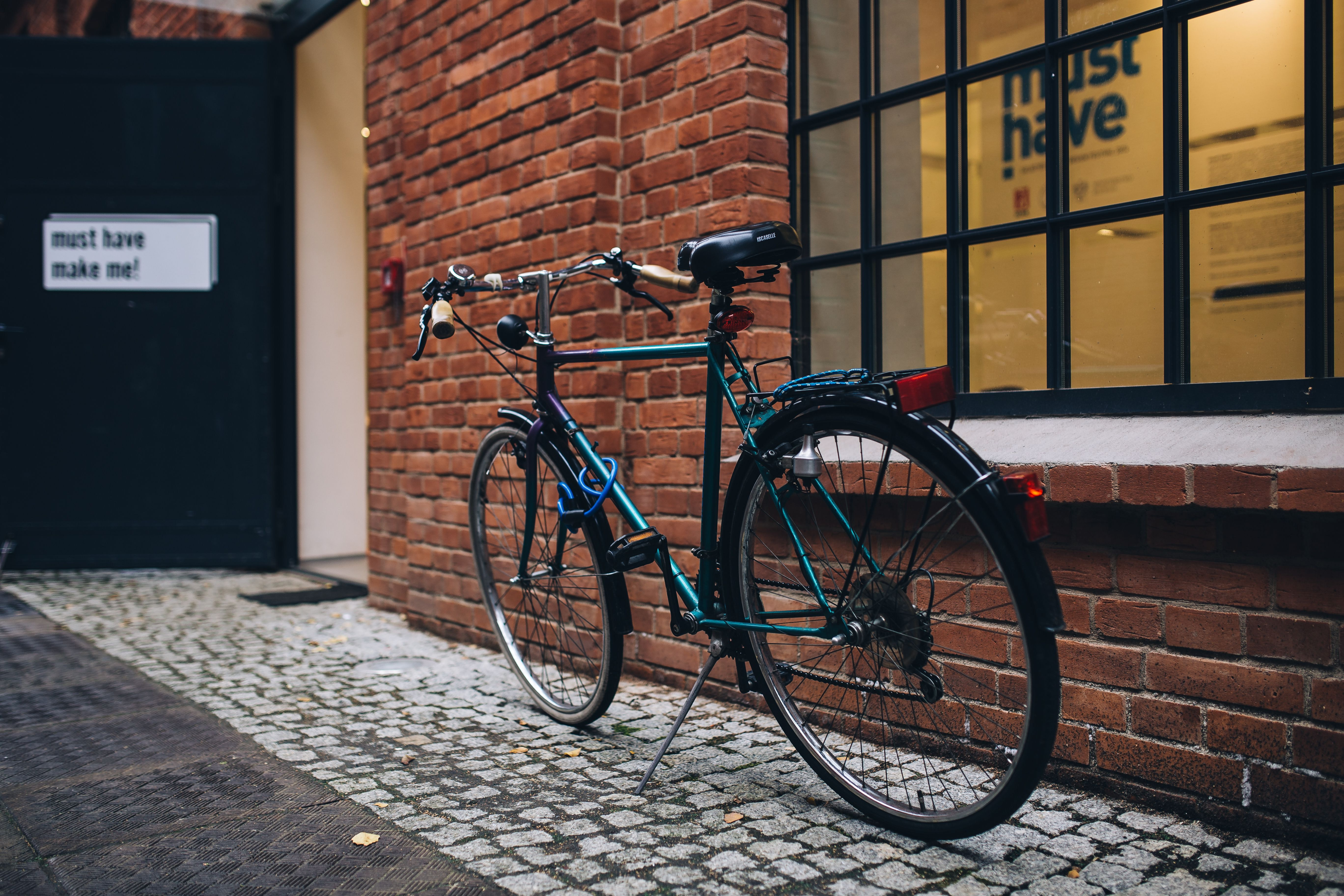 black and blue bicycle parked near a glass window at daytime