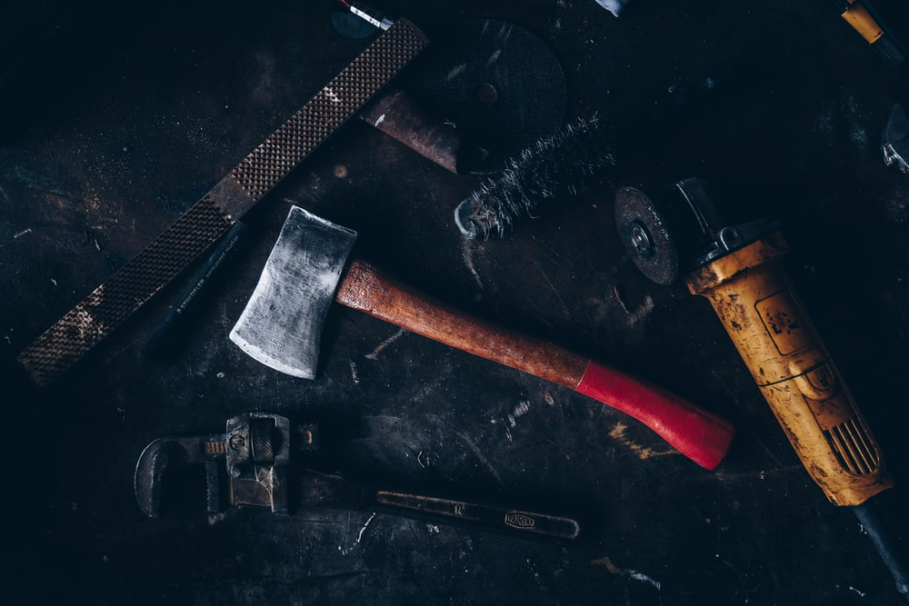 axe beside pipe wrench and angle grinder