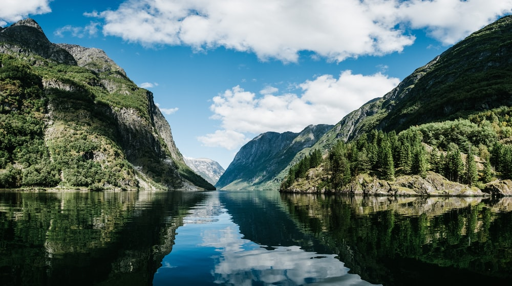 body of water near mountain under white clouds