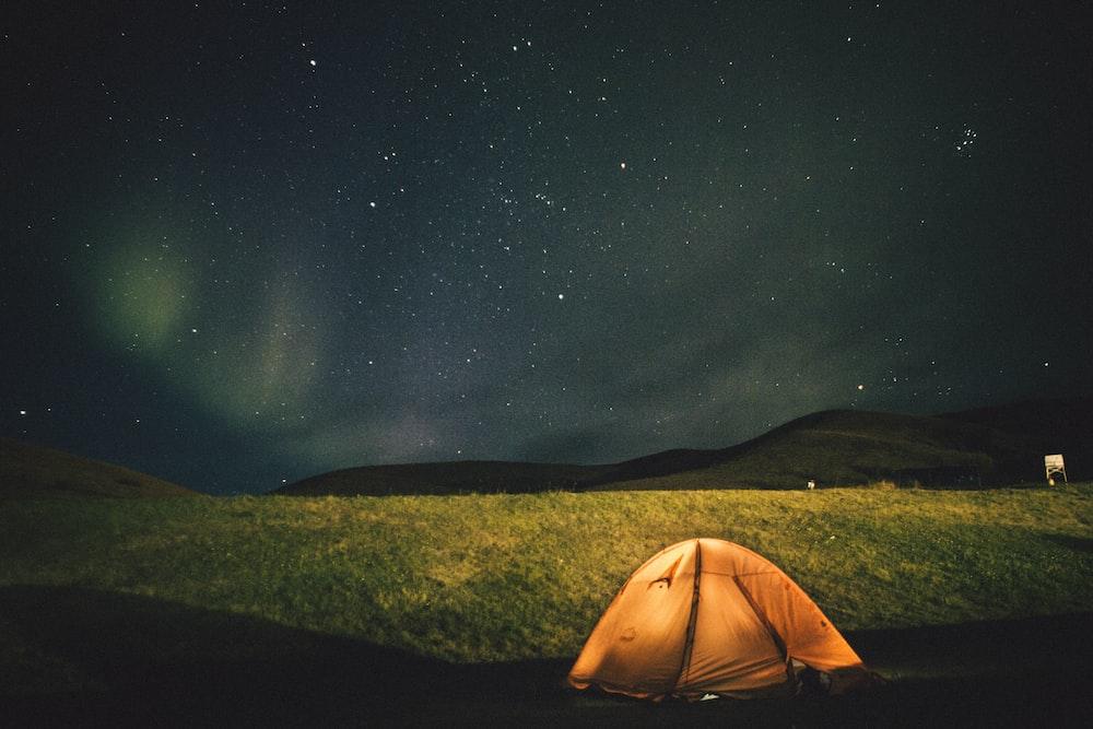 dome tent on grass field under stars