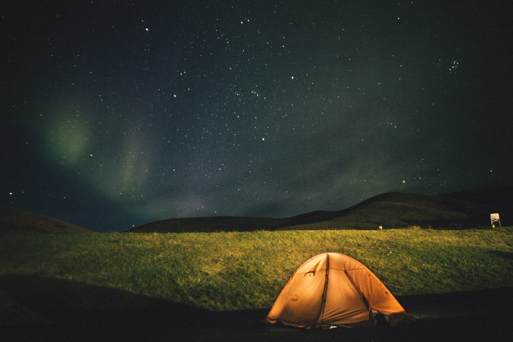 dome tent on grass field under stars